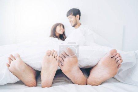 Photo pour Joyeux jeune couple relaxant dans la chambre à coucher après s'être réveillé le matin . - image libre de droit