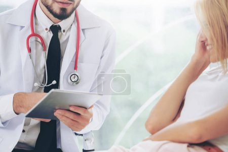 Photo pour Médecin de sexe masculin est parlant et en examinant la patiente au bureau de l'hôpital. Service de soins de santé et médical. - image libre de droit