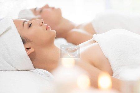 Photo pour Détendu de jeune femme allongée sur lit de spa préparé pour traitement facial et massage dans la station thermale de luxe. Bien-être, stress relief et rajeunissement concept. - image libre de droit