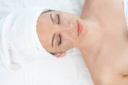 Photo for Relaxed young woman lying on spa bed prepared for facial treatment and massage in luxury spa resort. Wellness, stress relief and rejuvenation concept. - Royalty Free Image