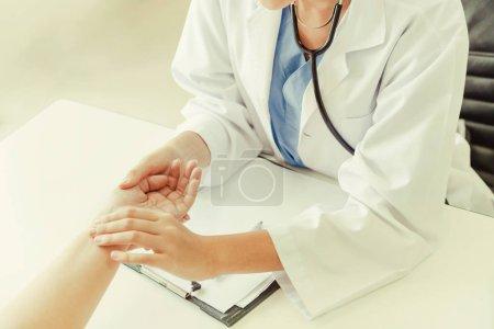 Photo pour Femme médecin parle à la patiente dans le bureau de l'hôpital tout en examinant le pouls des patients par les mains. Soins de santé et services médicaux . - image libre de droit