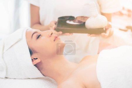 Photo pour Femme détendue allongée sur un lit de spa préparée pour un massage spa avec un thérapeute tenant un traitement spa en arrière-plan. Concept luxe bien-être, soulagement du stress et rajeunissement . - image libre de droit