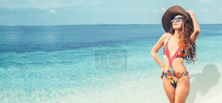 Photo for Happy young woman wearing swimsuit at tropical sand beach resort in summer for holiday travel vacation. - Royalty Free Image