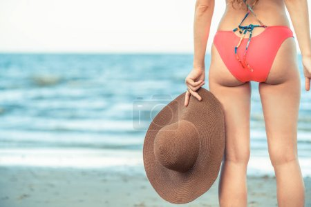 Photo for Happy young woman wearing swimsuit having good time at tropical beach in summer for holiday travel vacation. - Royalty Free Image