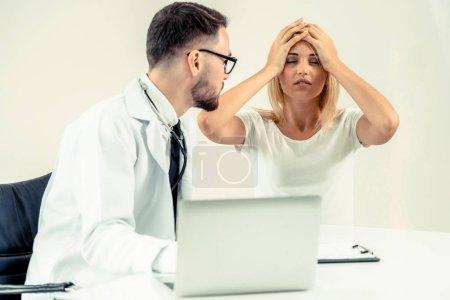 Photo pour Médecin de sexe masculin s'entretient avec la patiente dans le Bureau de l'hôpital tout en regardant les données de santé des patients sur l'ordinateur portable sur la table. Service de soins de santé et médical. - image libre de droit