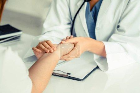 Photo pour Femme médecin parle à la patiente au bureau de l'hôpital tout en examinant le pouls des patients par les mains. Service de soins de santé et médical. - image libre de droit