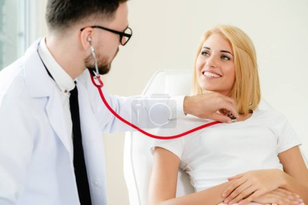 Photo for Male doctor is talking and examining female patient in hospital office. Healthcare and medical service. - Royalty Free Image