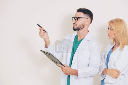 Photo pour Médecin chirurgical points sur espace copie vide lorsque vous êtes debout avec un autre médecin. Service médical et soins de santé concept. - image libre de droit