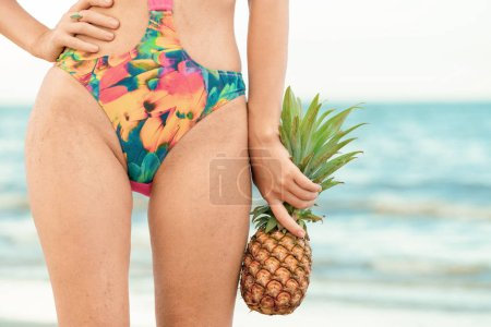 Photo for Happy young woman wearing swimsuit on tropical sand beach in summer for holiday travel vacation. - Royalty Free Image