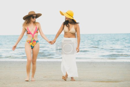 Photo for Happy women in bikinis go sunbathing together on tropical sand beach in summer vacation. Travel lifestyle. - Royalty Free Image