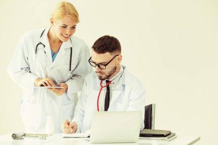 Photo pour Médecin au bureau de l'hôpital sur ordinateur portable sur la table de travail avec un autre médecin ayant la discussion sur la santé des patients. - image libre de droit