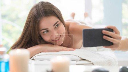 Photo pour Happy woman prend des photos selfie tout en étant couché sur un lit de spa pour un massage aromathérapie dans un spa de luxe avec un avant-plan flou de soins spa ensemble. Concept de bien-être et guérison . - image libre de droit