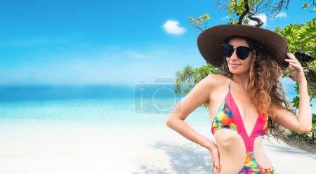 Photo pour Heureuse jeune femme porte le maillot de bain à resort de plage de sable tropicale en été pour des vacances vacances voyage. - image libre de droit