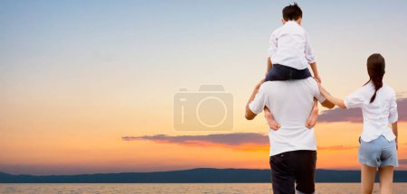 Photo for Happy family of mother and father carrying son on his shoulders on vacation. - Royalty Free Image