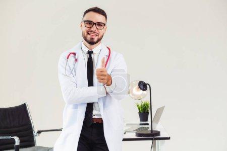 Photo pour Docteur en montrant des pouces vers le haut tout en travaillant à la table de bureau à l'hôpital. Concept de médecin et soins de santé. - image libre de droit