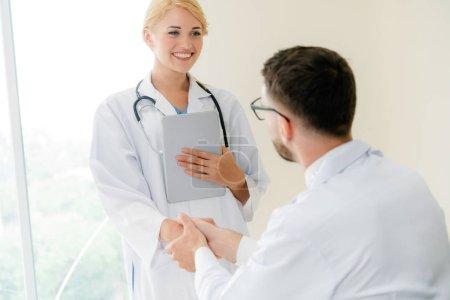 Photo pour Médecin à l'hôpital donnant poignée de main à un autre médecin montrant le succès et le travail d'équipe du personnel de santé professionnel . - image libre de droit