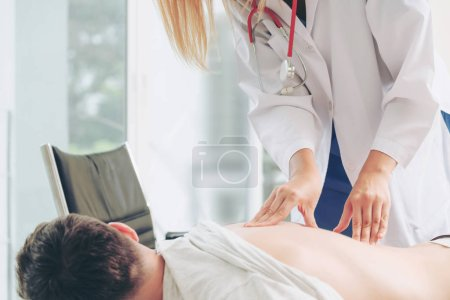 Photo pour Une femme médecin examine un patient de sexe masculin au bureau de l'hôpital. Soins de santé et services médicaux . - image libre de droit