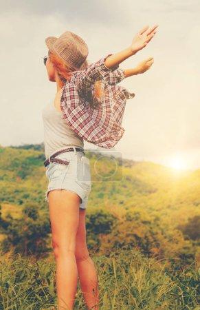 Photo pour Femme heureuse dans un champ vert et fond de montagne. Concept de liberté et de voyage . - image libre de droit