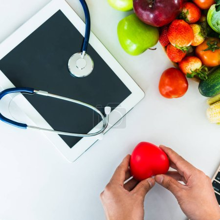 Photo for Diet food of fruit and vegetables for cholesterol control with nutritionist hands showing awareness and prevention of heart disease. Healthy eating and good nutrition concept. - Royalty Free Image