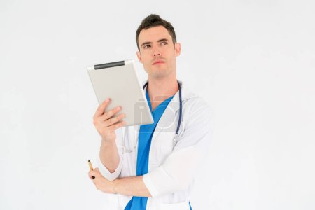 Photo pour Confiant beau docteur homme portant des uniformes sur fond blanc de l'hôpital. Service de soins de santé et médical. - image libre de droit