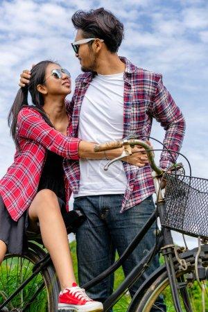 Photo pour Heureux jeune couple d'homme et de femme faire du vélo au champ d'herbe verte sur les collines. Concept de style de vie amour et voyage . - image libre de droit