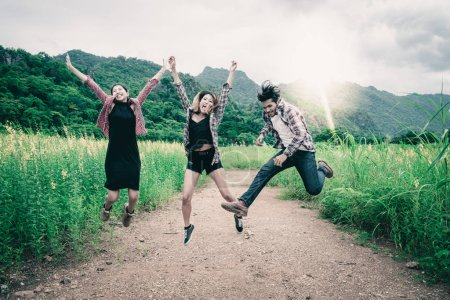 Group of happy young people jumping in the air while traveling in mountain and nature trail. Travel and outdoors lifestyle concept.