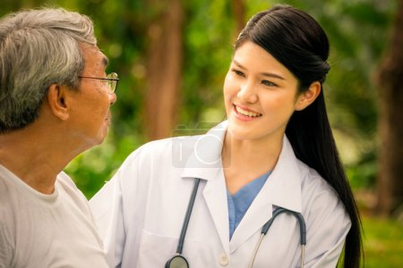 Photo for Friendly doctor taking care of senior man in the hospital garden. Medical and healthcare doctor service concept. - Royalty Free Image