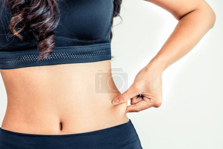 Photo for Young woman in sportswear touching her belly. Dieting and weight loss concept. - Royalty Free Image