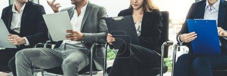 Photo pour Femmes et hommes d'affaires maintenant reprennent le dossier Cv en attendant sur des chaises de bureau pour entretien d'embauche. Concept entreprise de ressources humaines et des affaires. - image libre de droit