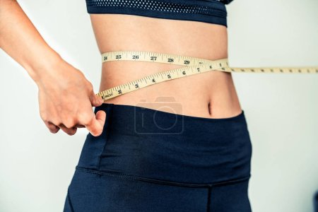 Photo for Close up shot of woman with slim body measuring her waistline and torso. Healthy nutrition and weight losing concept. - Royalty Free Image