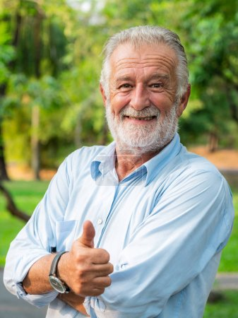 Photo for Portrait of happy senior man standing in the park. Elder health and retirement concept. - Royalty Free Image