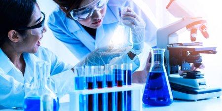 Photo pour Groupe de scientifiques portant une blouse de laboratoire travaillant en laboratoire tout en examinant un échantillon de biochimie dans une éprouvette et des instruments scientifiques. Science technologie recherche et développement concept d'étude. - image libre de droit