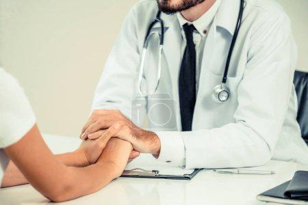 Photo pour Homme médecin apaise une patiente dans le bureau de l'hôpital tout en tenant les patients par la main. Soins de santé et services médicaux . - image libre de droit