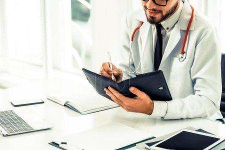 Photo pour Docteur en lisant en écrivant note sur un livre au bureau, à l'hôpital. Concept de médecin et soins de santé. - image libre de droit