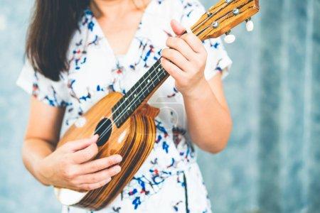 Photo pour Musicien de femme heureuse ukulele de jouer et chanter une chanson dans son studio. Concept de musique lifestyle. - image libre de droit