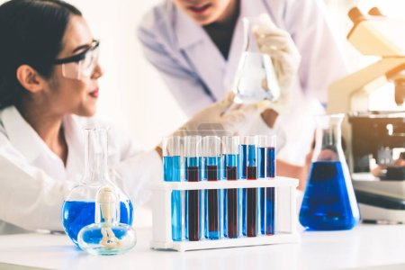 Photo for Group of scientists wearing lab coat working in laboratory while examining biochemistry sample in test tube and scientific instruments. Science technology research and development study concept. - Royalty Free Image