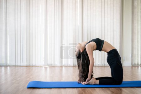 Young woman practicing yoga position in an indoor ...