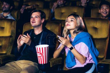 Photo pour Groupe de spectateurs heureux et amusant regarder le cinéma dans le cinéma. Activité récréative de groupe et concept de divertissement. - image libre de droit
