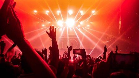 Photo pour Les gens heureux dansent dans le concert de soirée DJ de boîte de nuit et écoutent la musique de danse électronique de DJ sur la scène. Silhouette foule joyeuse fête le Nouvel An 2020. Style de vie des gens DJ vie nocturne. - image libre de droit