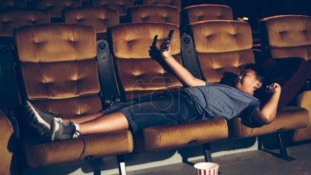 Photo pour Un garçon allongé et jouant à un jeu et prenant une photo au cinéma - image libre de droit
