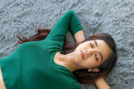 Photo for Happy Asian couple lying together on carpet at living room floor. Love relationship and lifestyle concept. - Royalty Free Image