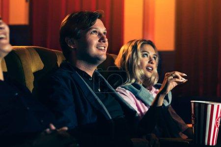 Photo pour Amant caucasien et femme assise à côté d'eux appréciant de regarder le film - image libre de droit