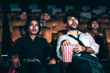 Photo for Audience sitting in a cinema and watching terrible horror. Afraid woman sitting near a man is shock and scare - Royalty Free Image