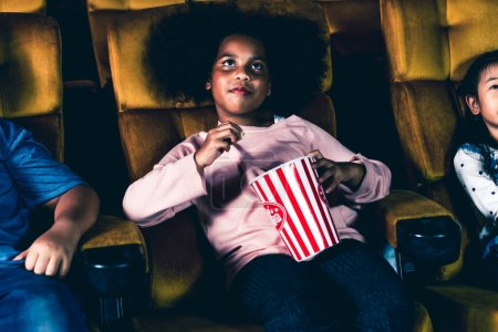 Photo pour Trois enfants s'amusent et aiment regarder des films au cinéma - image libre de droit