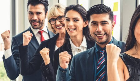 Photo pour Des gens d'affaires prospères debout ensemble montrant une forte relation de la communauté des travailleurs. Une équipe d'hommes d'affaires et de femmes d'affaires exprimant un solide travail d'équipe au bureau moderne. - image libre de droit