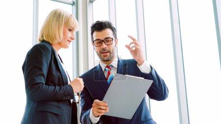 Foto de Dos empresarios hablan de la estrategia del proyecto en la sala de reuniones de la oficina. Empresario discutir la planificación del proyecto con su colega en el lugar de trabajo moderno, mientras que tener conversación y asesoramiento sobre el informe de datos financieros. - Imagen libre de derechos