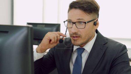 Photo pour Des gens d'affaires portant un casque qui travaillent au bureau pour soutenir un client ou un collègue à distance. Le centre d'appels, le télémarketing, l'agent de soutien à la clientèle fournissent le service par vidéoconférence téléphonique. - image libre de droit
