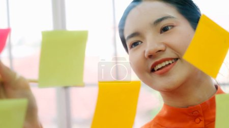 Photo for Business people work on project planning board in office and having conversation with coworker friend to analyze project development . They use sticky notes posted on glass wall to make it organized . - Royalty Free Image