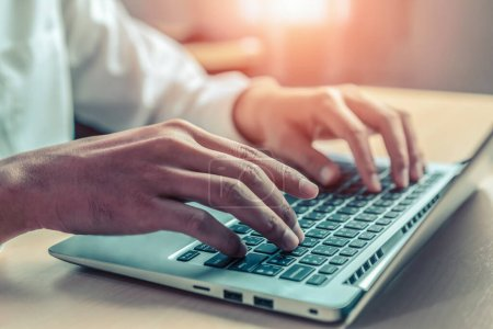 Photo for Businessman hand typing on computer keyboard of a laptop computer in office. Business and finance concept. - Royalty Free Image