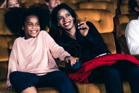 Photo pour Femme profiter de regarder un film avec sa fille au cinéma sourire et rire ensemble - image libre de droit
